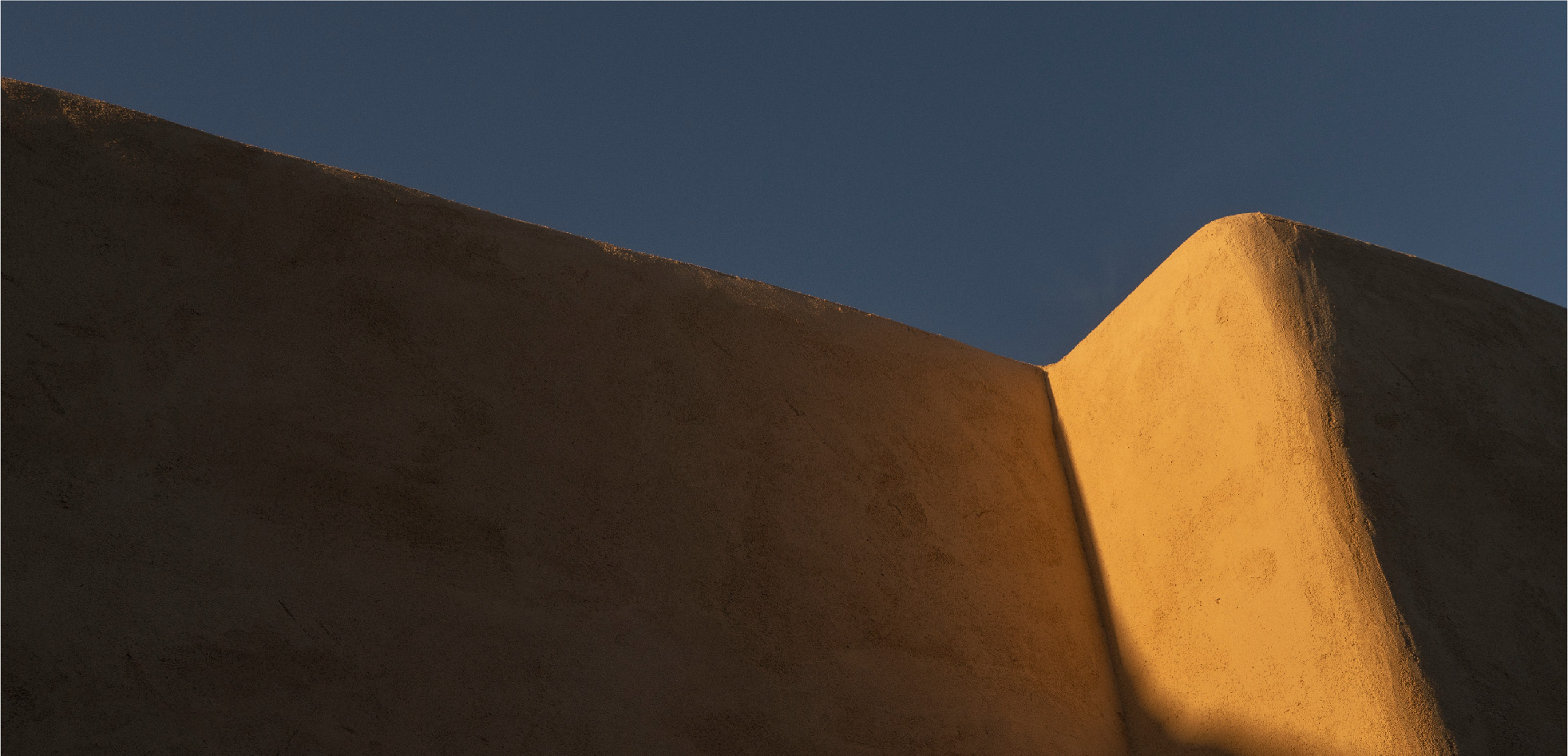 Smooth tan stucco against a blue sky.