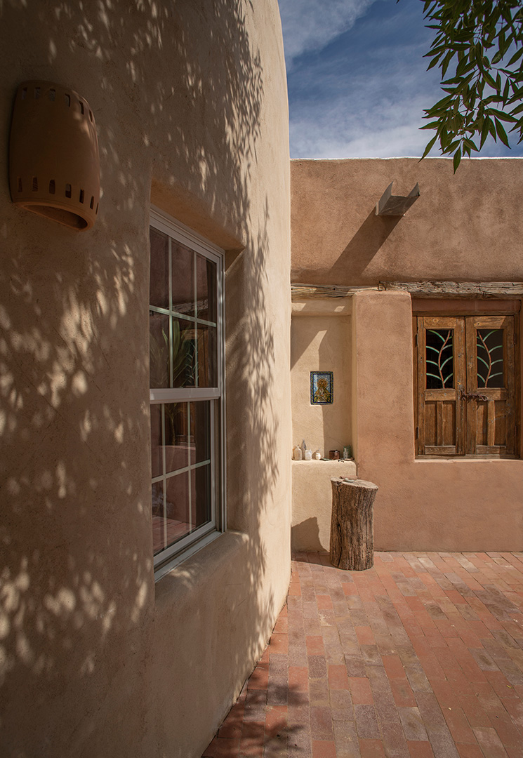 Brown stucco with window, shady tree and hand-carved wooden door