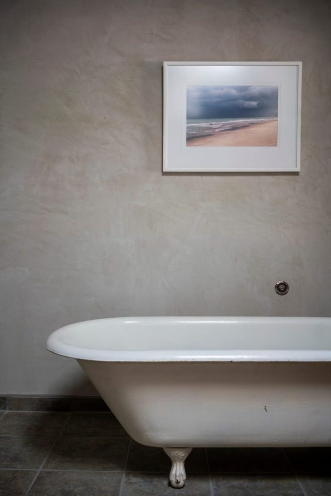 Satin-textured plaster wall behind claw-foot tub